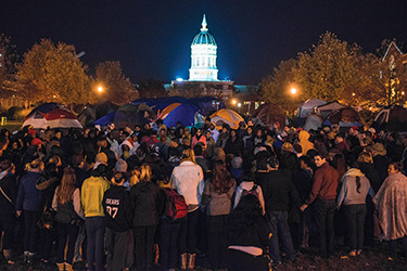 A large gathering circles up for group prayer for hunger striker Jonathan Butler and the community at the tent camp November 8, 2015, on the University of Missouri campus. This assembly occurred the same weekend the Missouri football team announced it wouldn't play until Butler's hunger strike ended. The next morning, UM system President Tim Wolfe announced his resignation, followed shortly after by Chancellor Bowen Loftin. (Photo ©Justin L. Stewart)
