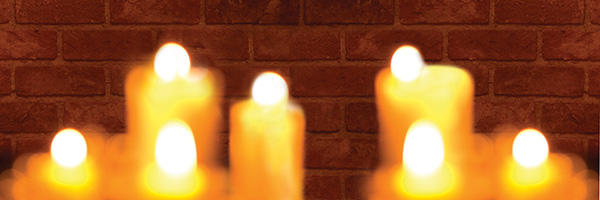 Candles burning in front of a brick wall