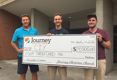 Representatives of Journey Christian Church, Roswell, GA, present a check to Christ In Youth after selling the church's building.